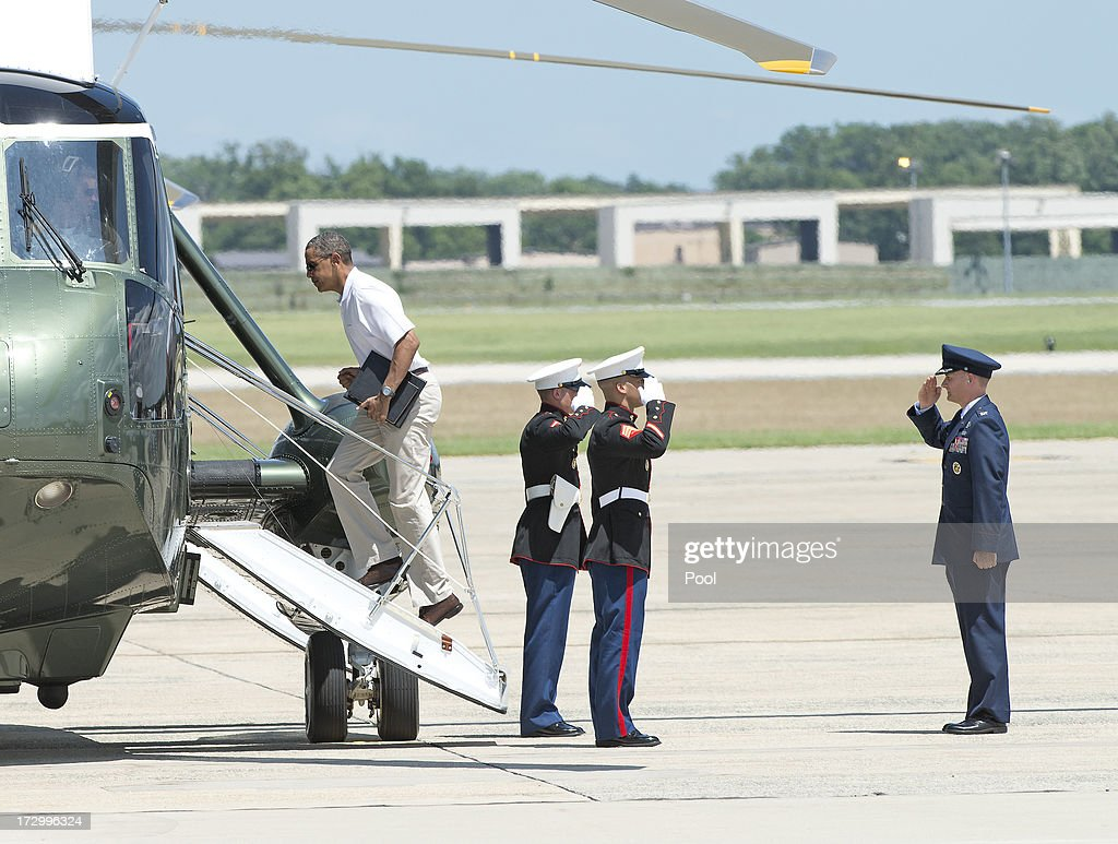 U.S. President Barack Obama is saluted by the U.S. Marine Guards and a U.S. Air Force Officer as he boards Marine 1 to depart Joint Base Andrews on July 5, 2013 near Camp Springs, Maryland. Obama is heading to Camp David following a round of golf.