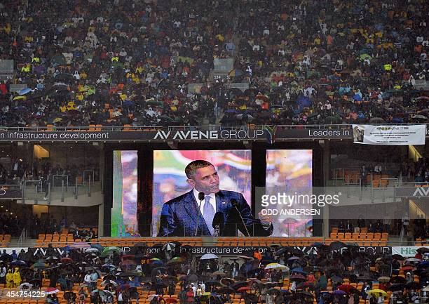 US President Barack Obama is seen on a giant screen as he gives a speech during the memorial service of South African former president Nelson Mandela...