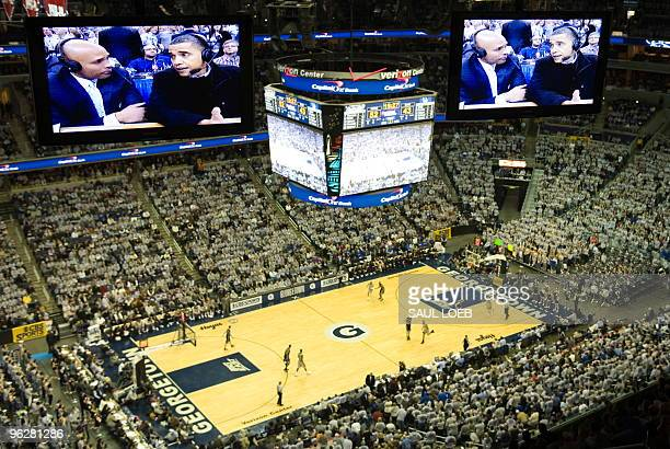 US President Barack Obama is seen on television while talking with CBS commentators courtside during the second half of the NCAA men's college...