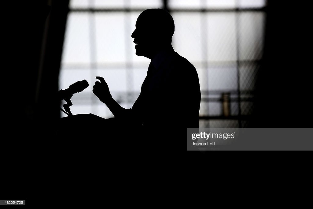U.S. President Barack Obama is silhouetted as he speaks about his proposal to raise the federal minimum wage at the University of Michigan on April 2, 2014 in Ann Arbor, Michigan. Obama said every American deserves a fair working wage.