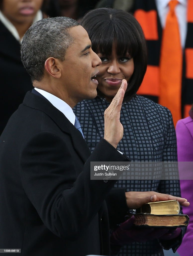 U.S. President Barack Obama (L) is sworn in as First lady Michelle Obama looks on during the public ceremonial inauguration on the West Front of the U.S. Capitol January 21, 2013 in Washington, DC. Barack Obama was re-elected for a second term as President of the United States.