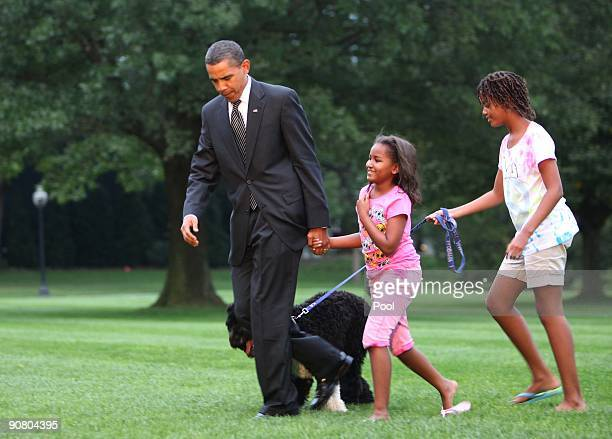 President Barack Obama is welcomed home from daughters Sasha Malia and dog Bo on the South lawn of the White House September 15 2009 in Washington DC...