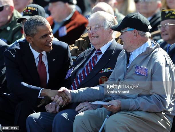 S President Barack Obama joins WWII Veterans during a ceremony at the Normandy American Cemetery on the 70th anniversary of DDay June 6 2014 in...