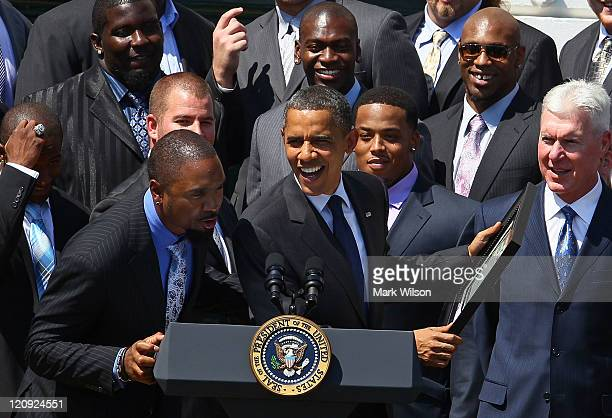 S President Barack Obama jokes with Charles Woodson after recieving a ownership certificate during a reception for the National Football League Super...