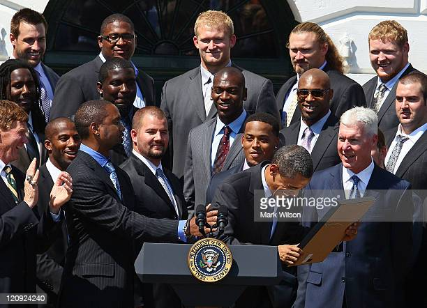 S President Barack Obama jokes with cornerback Charles Woodson after recieving an ownership certificate from the cornerback during a reception for...
