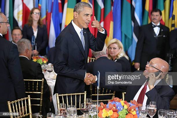 President Barack Obama jokes with South African President Jacob Zuma, who was talking on the phone, during a luncheon hosted by United Nations...