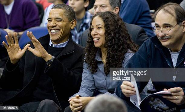 US President Barack Obama jokes with the referee to give him the ball as he sits alongside Mona Sutphen White House deputy chief of staff and David...