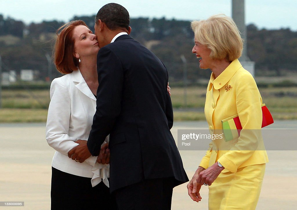 U.S. President Barack Obama kisses Australian Prime Minister Julia Gillard (L) as Australian Governor General Quentin Bryce (R) laughs during his arrival at Fairbairn Defence Establishment on the first day of his 2-day visit to Australia, on November 16, 2011 in Canberra, Australia. The President will today receive a Cermeonial Welcome, attend a bi-lateral meeting and hold a joint media conference with Julia Gillard, and attend a Parliamentary Dinner this evening, before addressing Parliament and heading to Darwin tomorrow.