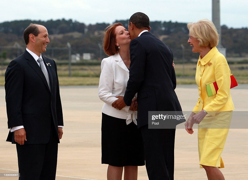 U.S. President Barack Obama kisses Australian Prime Minister Julia Gillard (2nd L) as Australian Governor General Quentin Bryce (R) and US Ambassador to Australia Jeffrey Bleich (L) laugh during his arrival at Fairbairn Defence Establishment on the first day of his 2-day visit to Australia, on November 16, 2011 in Canberra, Australia. The President will today receive a Cermeonial Welcome, attend a bi-lateral meeting and hold a joint media conference with Julia Gillard, and attend a Parliamentary Dinner this evening, before addressing Parliament and heading to Darwin tomorrow.