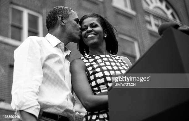 President Barack Obama kisses First Lady Michelle Obama as they arrive to deliver remarks during a campaign event at the Alliant Energy Amphitheater...