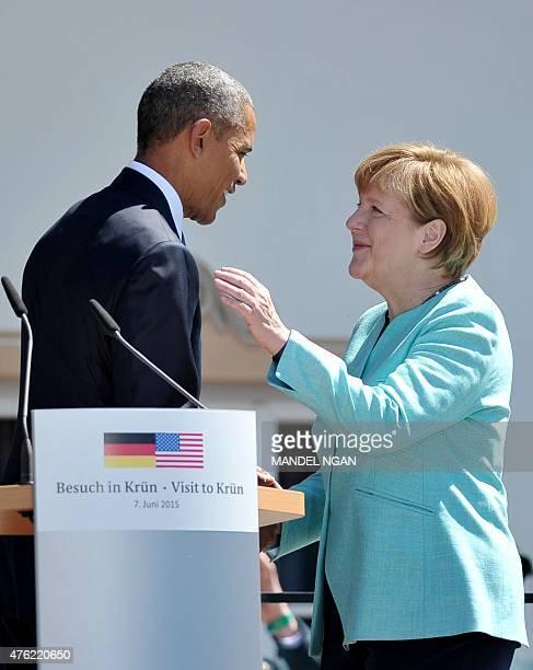 President Barack Obama kisses Germany's Chancellor Angela Merkel after delivering his speech in the village of Kruen near Garmisch-Partenkirchen on...