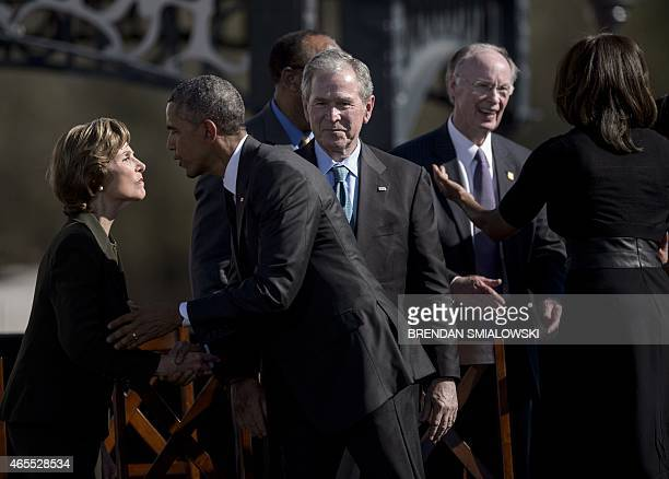 US President Barack Obama kisses Laura Bush while former US President George W Bush watches and Alabama Governor Robert J Bentley and US first lady...