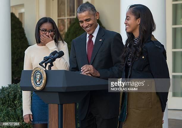 US President Barack Obama laughs with daughters Malia and Sasha before 'pardoning' the National Thanksgiving Turkey in the Rose Garden at the White...