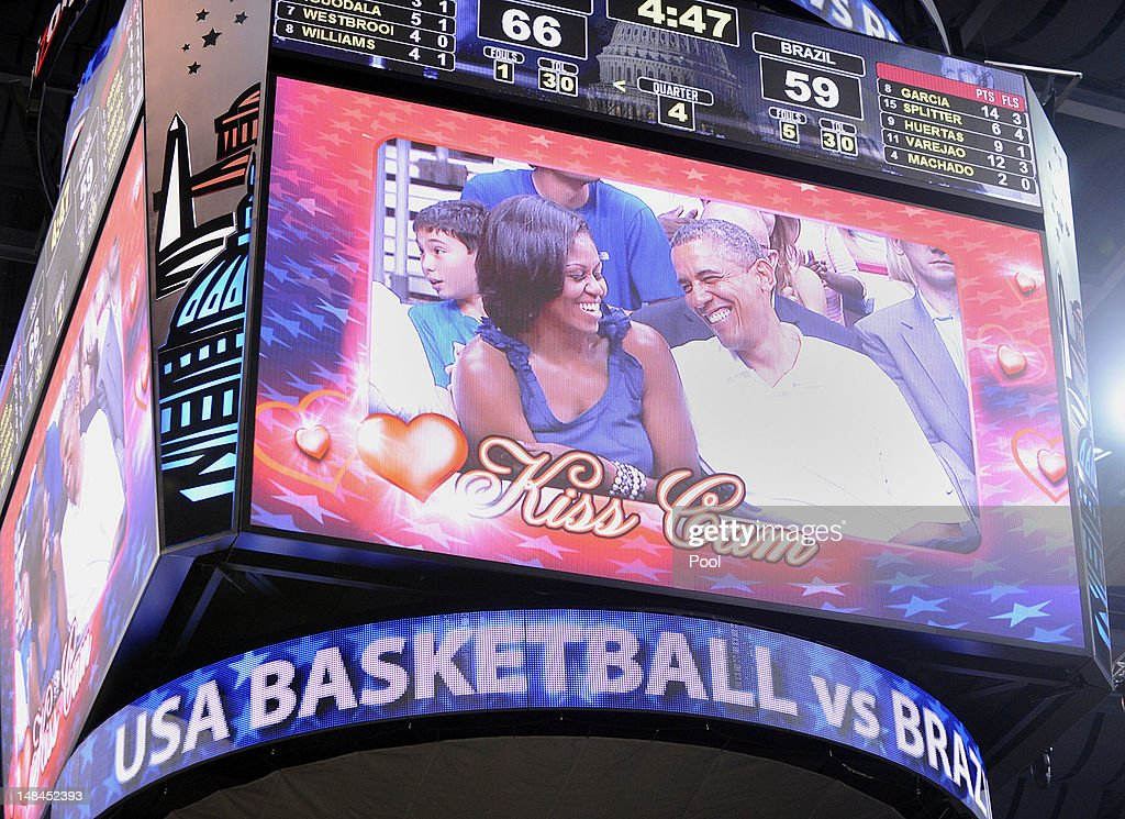 U.S. President Barack Obama laughs with first lady Michelle Obama as they appear on the 'Kiss Cam' as the US Senior Men's National Team and Brazil play during a pre-Olympic exhibition basketball game at the Verizon Center on July 16, 2012 in Washington, DC.