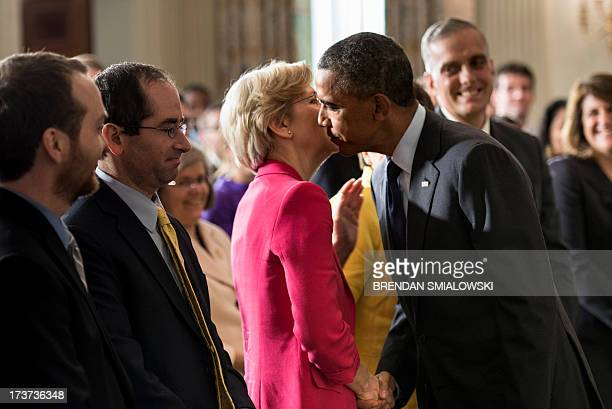 US President Barack Obama leans in to kiss Senator Elizabeth Warren after making a statement in the State Dining Room of the White House July 17 2013...