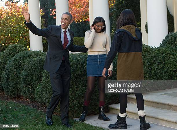 US President Barack Obama leaves with daughters Malia and Sasha after 'pardoning' the National Thanksgiving Turkey in the Rose Garden at the White...