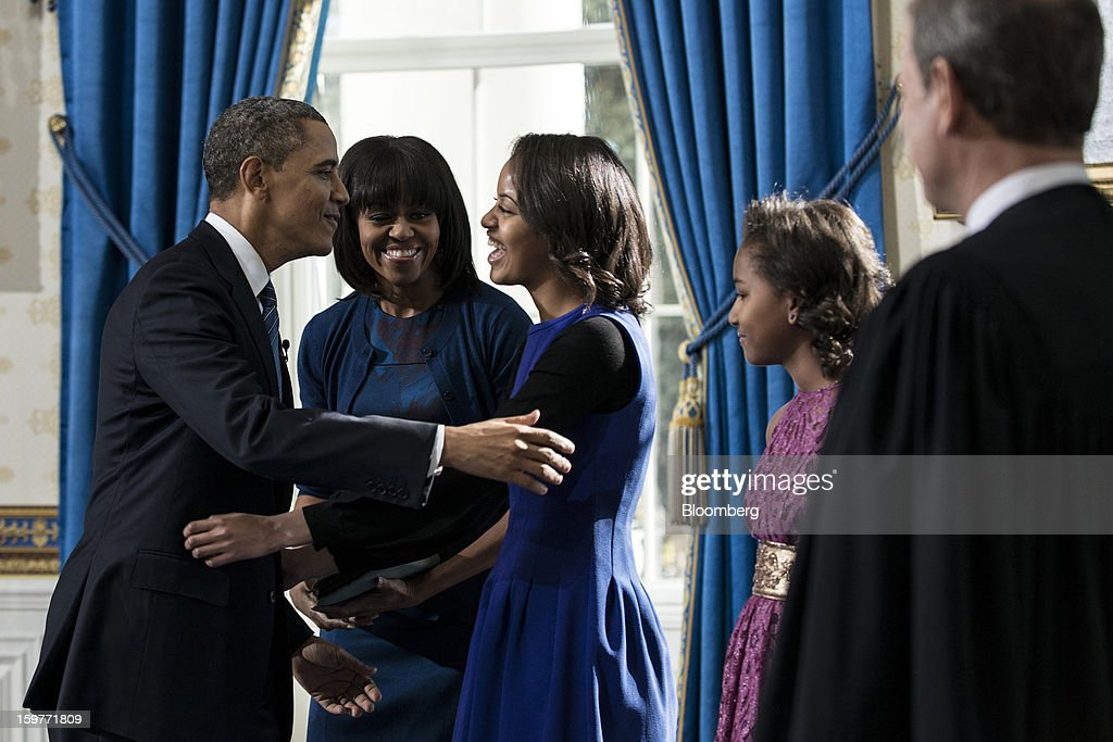 U.S. President Barack Obama, left, embraces his daughter Malia Obama, center, as first lady Michelle Obama, second from left, daughter Sasha Obama, second from right, and Supreme Court Chief Justice John Roberts watch after being sworn in for a second term in the Blue Room of the White House in Washington, D.C., U.S., on Sunday, Jan. 20, 2013. As he enters his second term Obama has shed the aura of a hopeful consensus builder determined to break partisan gridlock and adopted a more confrontational stance with Republicans. Photographer: Brendan Smialowski/Pool via Bloomberg