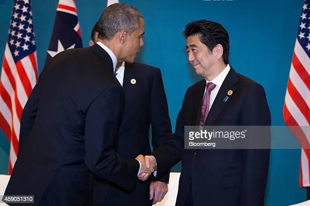 US President Barack Obama left shakes hands with Shinzo Abe Japan's prime minister right as Tony Abbott Australia's prime minister center stands...