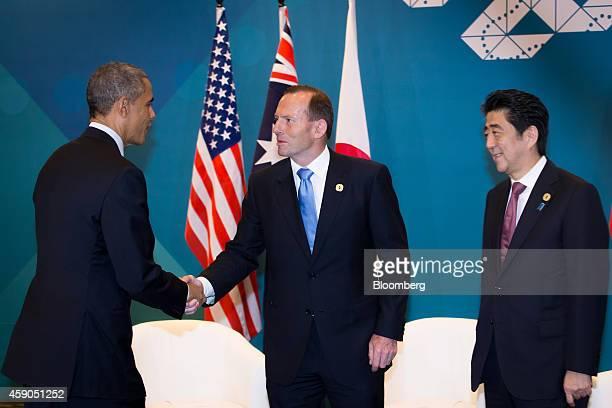 US President Barack Obama left shakes hands with Tony Abbott Australia's prime minister center as Shinzo Abe Japan's prime minister looks on during a...