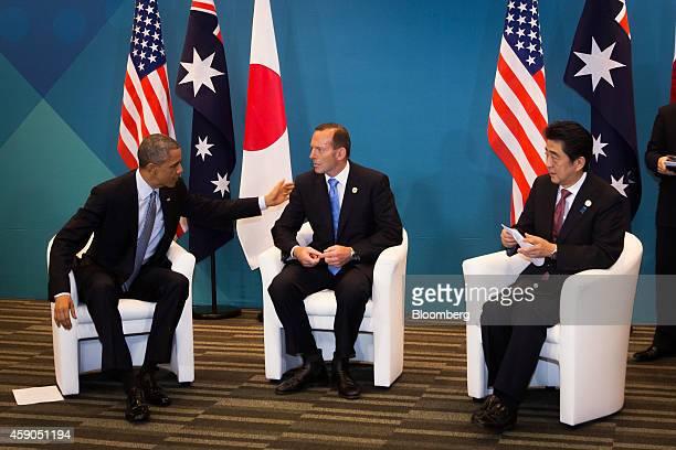 US President Barack Obama left speaks with Tony Abbott Australia's prime minister center as Shinzo Abe Japan's prime minister looks on during a...