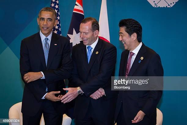 US President Barack Obama left Tony Abbott Australia's prime minister center and Shinzo Abe Japan's prime minister shake hands during a trilateral...