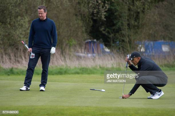 US President Barack Obama lines up a putt as British Prime Minister David Cameron looks on from the 3rd green at The Grove Golf Course near Watford...