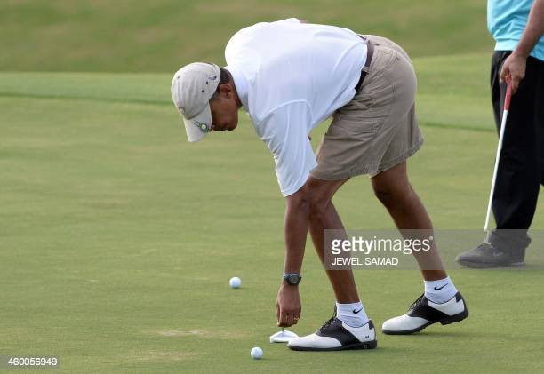 US President Barack Obama lines up his putt at 18th green as he plays golf at MidPacific Country Club in Kailua Hawaii on January 1 2014 The first...