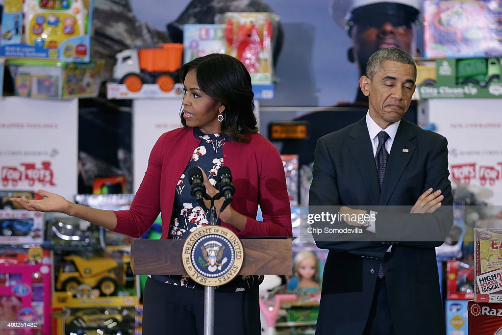 U.S. President Barack Obama listens as first lady Michelle Obama delivers remarks before sorting toys and gifts donated by Executive Office of the President staff to the Marine Corps Reserve Toys for Tots Program at Joint Base Anacostia-Bolling December 10, 2014 in Washington, DC. For 67 years the Toys for Tots program has worked with local communities to collect and distribute toys and gifts for less fortunate children throughout the United States.