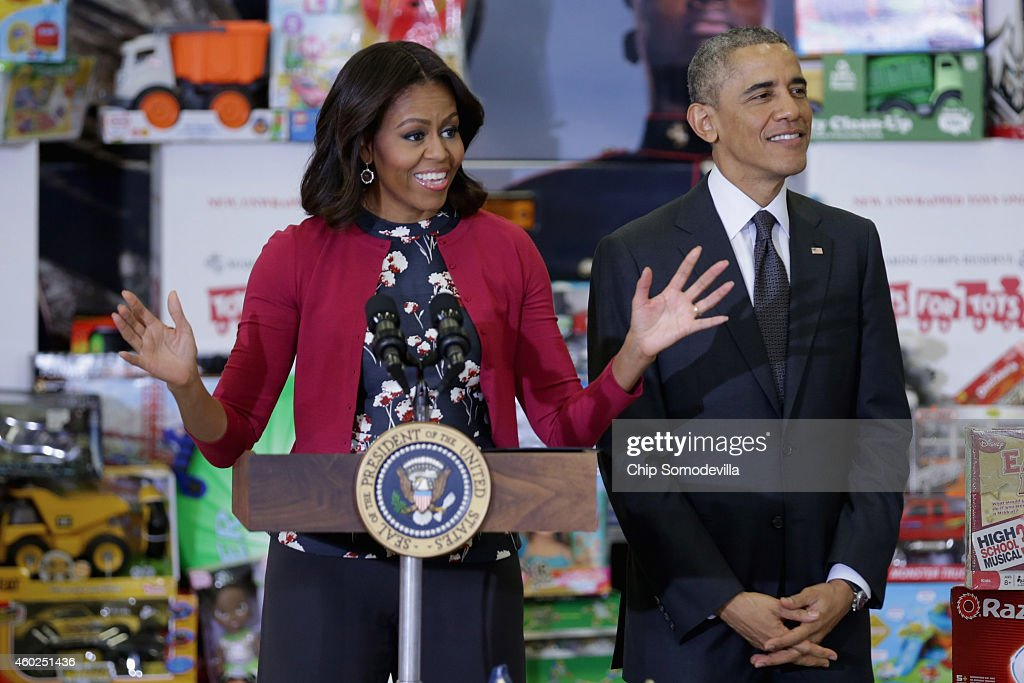 US President Barack Obama listens as first lady Michelle Obama delivers remarks before sorting toys and gifts donated by Executive Office of the President staff to the Marine Corps Reserve Toys for Tots Program at Joint Base Anacostia-Bolling December 10, 2014 in Washington, DC. For 67 years the Toys for Tots program has worked with local communities to collect and distribute toys and gifts for less fortunate children throughout the United States.