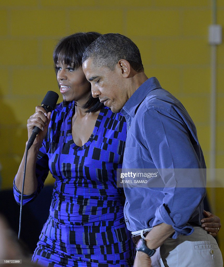 US President Barack Obama (R) listens as First Lady Michelle Obama speaks to a crowd at Burrville Elementary School after participating in National Day of Service on January 19, 2013 in Washington DC, as part of the 57th Presidential Inauguration. Americans across the country participate in service projects in their communities to celebrate the legacy of civil rights leader Dr. Martin Luther King, Jr. The holiday honoring King will be observed on January 21, the day of the second inauguration of US President Barack Obama and Vice President Biden. AFP PHOTO/Jewel Samad