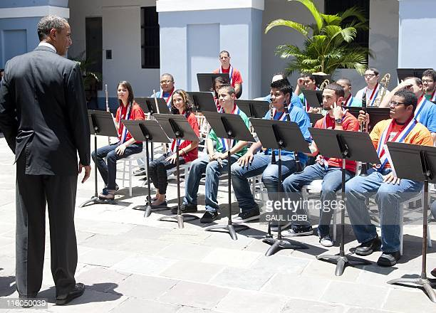 US President Barack Obama listens as students play in a courtyard during a tour of La Fortaleza the oldest governor's mansion in the Western...