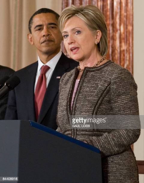 President Barack Obama listens as US Secretary of State Hillary Clinton speaks at the State Department in Washington, DC, January 22, 2009. Obama...