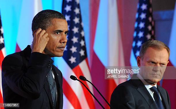 US President Barack Obama listens to a question as Polish Prime Minister Donald Tusk looks on during a joint press conference following their meeting...