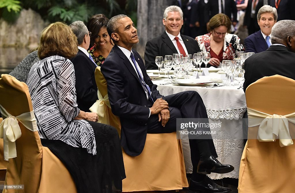 US President Barack Obama (front) listens to music as First Lady Michelle Obama chats with Cuban President Raul Castro during the state dinner at the Revolution Palace in Havana on March 21, 2016. Obama and Castro vowed Monday in Havana to set aside their differences in pursuit of what the US president called a 'new day' for the long bitterly divided neighbors. AFP PHOTO/Nicholas Kamm / AFP / NICHOLAS
