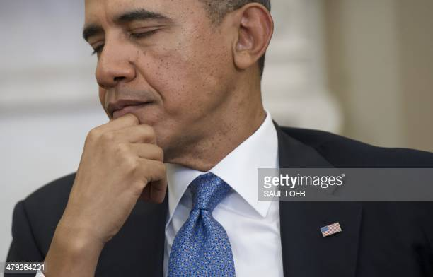 US President Barack Obama listens to Palestinian President Mahmud Abbas as they hold meetings in the Oval Office of the White House in Washington DC...