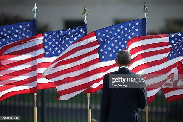 S President Barack Obama listens to the national anthem during a ceremony to mark the 13th anniversary of the 9/11 terrorists attacks at the Pentagon...