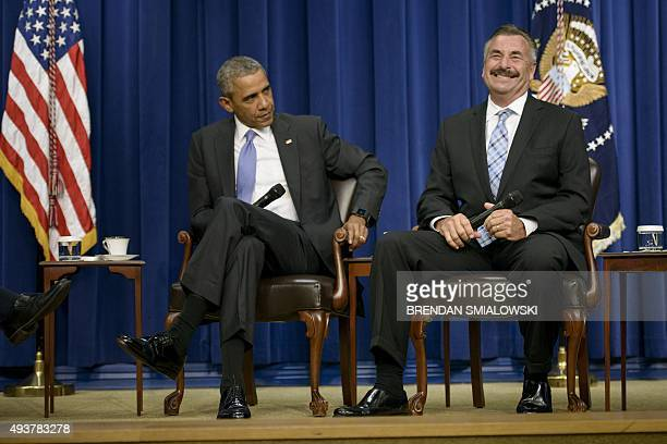 President Barack Obama listens while Charlie Beck , Chief of the Los Angeles Police Department, laughs at Beck's joke about always knowing why he has...