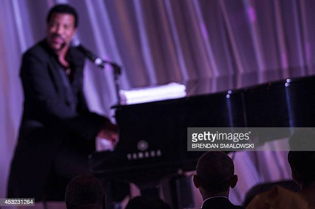 US President Barack Obama listens while Lionel Richie performs during a dinner for participants of the US Africa Leaders Summit August 5 2014 in...