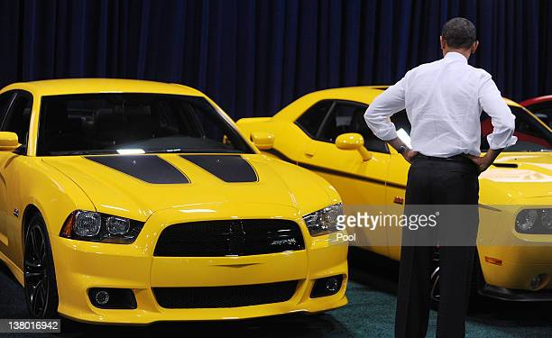 US President Barack Obama looks at a Dodge Charger during a visit to the DC Auto Show at the Convention Center January 31 2012 in Washington DC Obama...