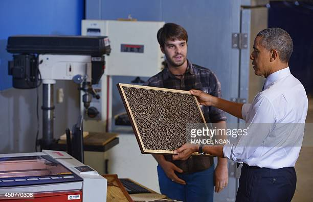 US President Barack Obama looks at a panel produced from a laser engraving maching during a tour of TechShop Pittsburgh on June 17 2014 in Pittsburgh...