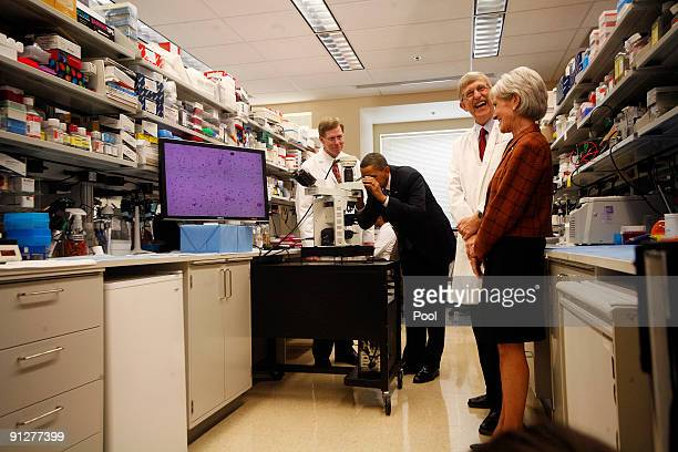 US President Barack Obama looks at brain cells into a microscope during a during a laboratory tour with Health and Human Services Secretary Kathleen...