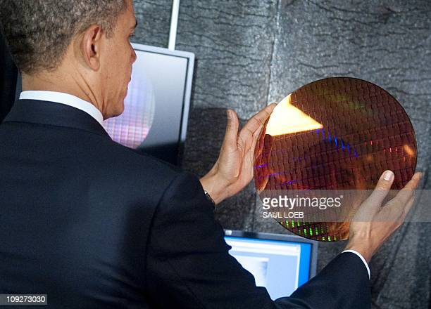 US President Barack Obama looks at his reflection as he holds an Intel wafer made of microchips while touring a semiconductor manufacturing facility...