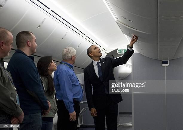 US President Barack Obama looks at the overhead bin in a Boeing 787 Dreamliner airplane that will be delivered to United Airlines during a tour of...