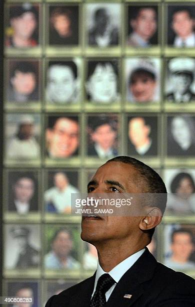 US President Barack Obama looks at the pictures of 9/11 victims as he tours the National September 11 Memorial Museum on May 15 2014 in New York...