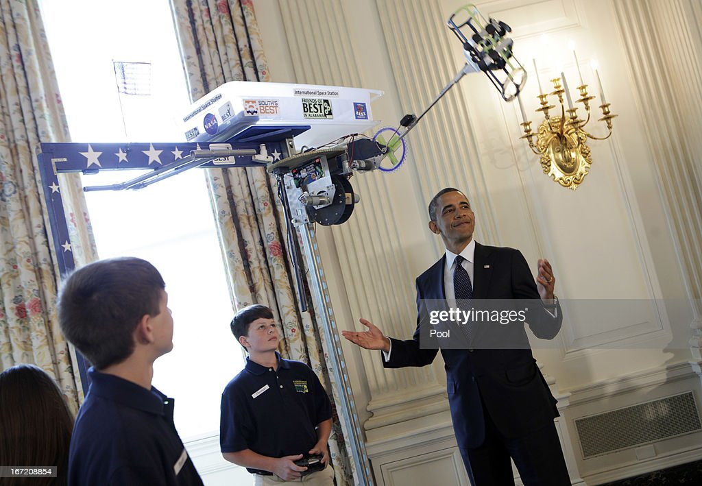 U.S. President Barack Obama looks at the Robot 'Vator' created and presented by Victoria Flechter, Rush Lyons, and Thomas Shields from St Vincent de Paul, Theodore Alabama in the State Dining Room of the White House during the White House Science Fair April 22, 2013 in Washington, DC. The White House Science Fair celebrates the student winners of a broad range of science, technology, engineering and math (STEM) competitions from across the country. The first White House Science Fair was held in late 2010.