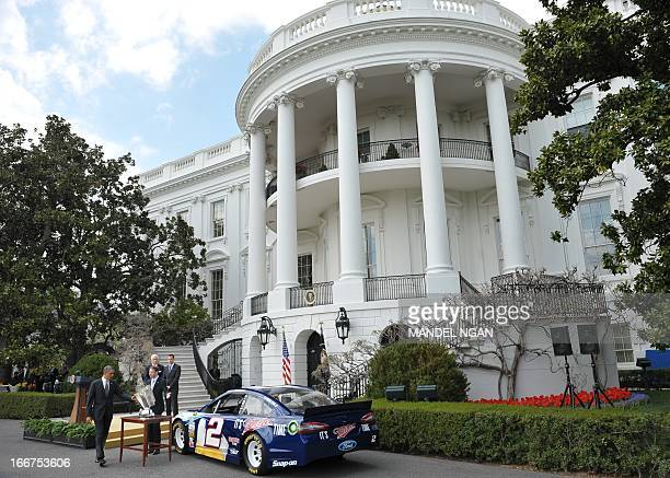 President Barack Obama looks at the trophy as NASCAR Sprint Cup Series champion Brad Keselowski shows him his car on the South Lawn of the White...