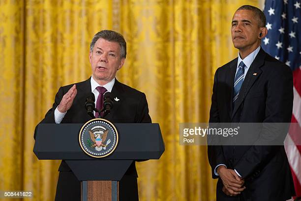 President Barack Obama looks on as Colombia President Juan Manuel Santos delivers remarks at a reception marking 15 years of Plan Colombia, in the...