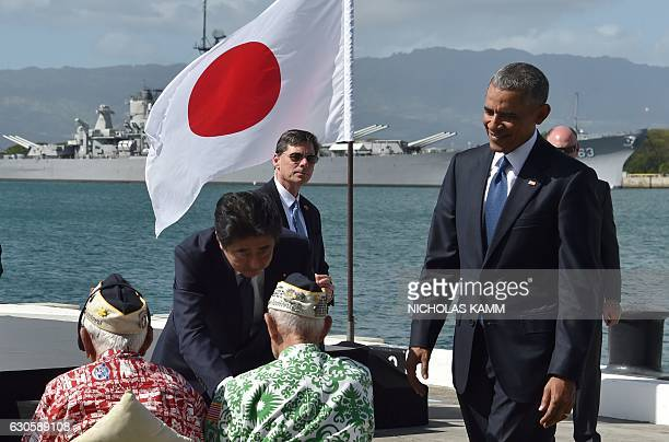 US President Barack Obama looks on as Japanese Prime Minister Shinzo Abe shakes hands with veterans at Kilo Pier overlooking the USS Arizona Memorial...