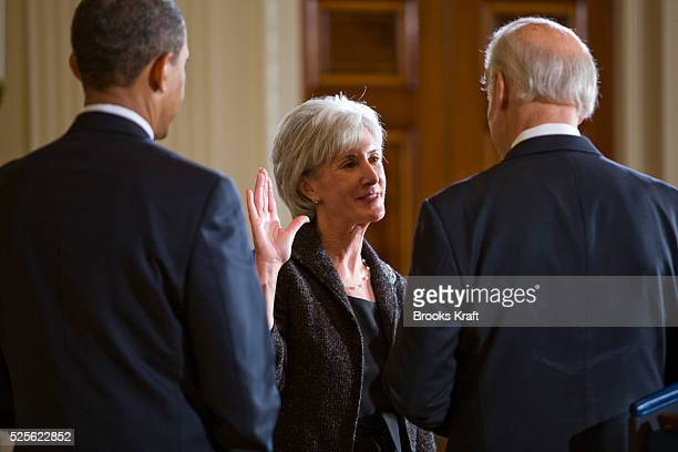 President Barack Obama looks on as Vice President Joe Biden ceremonially swears in Health and Human Services Secretary Kathleen Sebelius in the East...