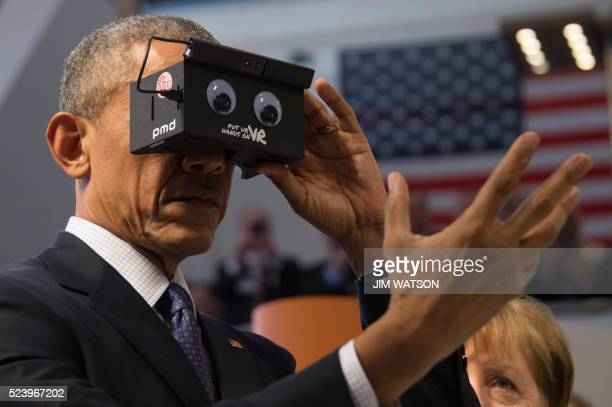 US President Barack Obama looks through a virtual reality device at the booth of German automation company ifm electronic as he tours with the German...